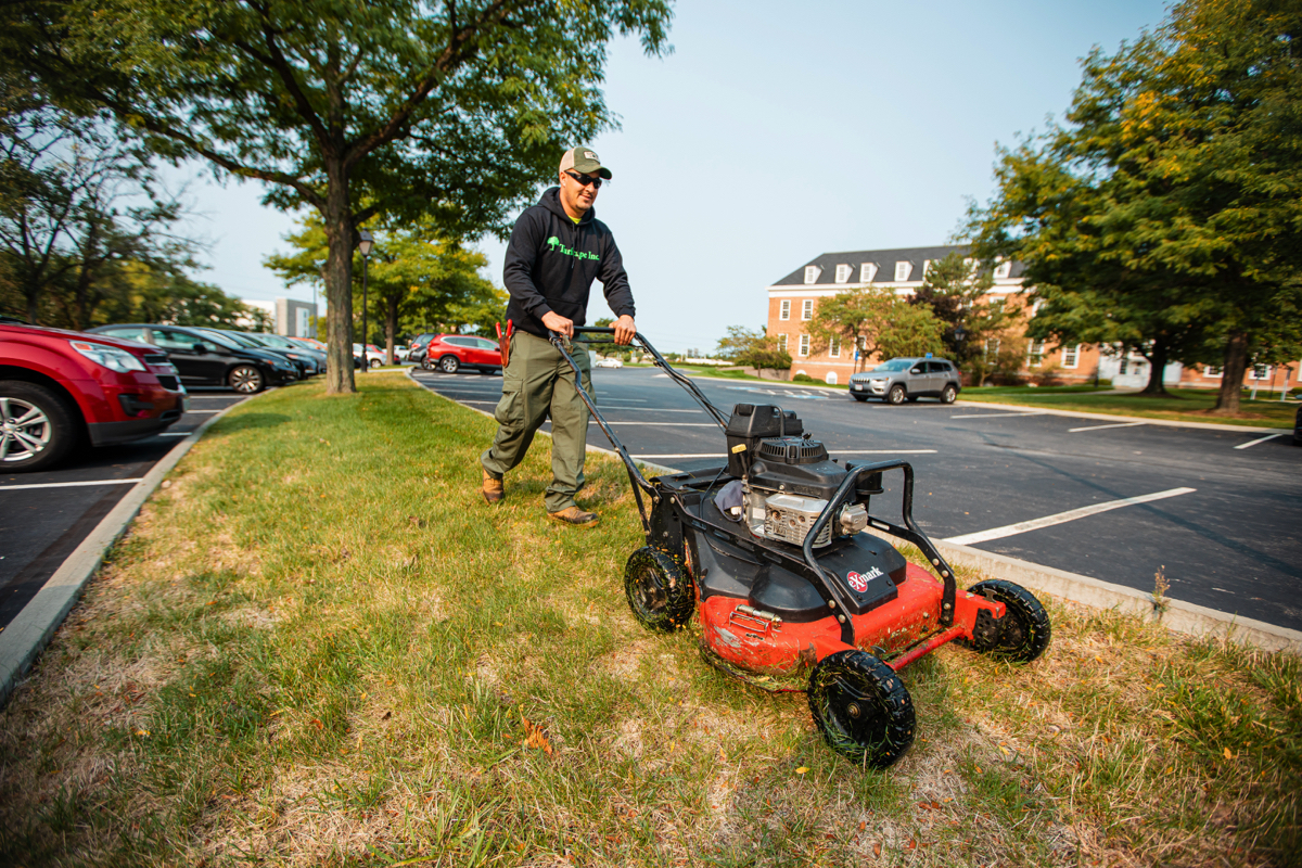 Commercial Landscaping Crew mowing along a parking lot