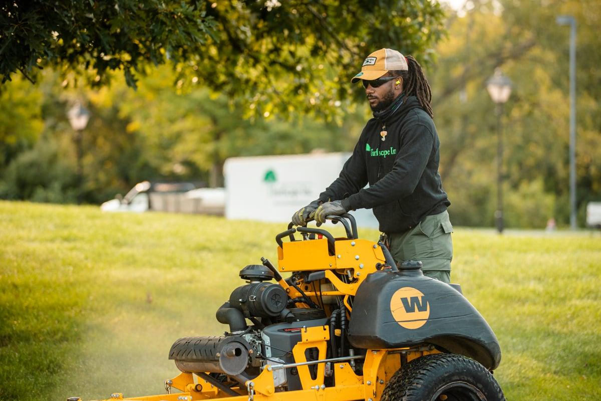 lawn care professional mows lawn