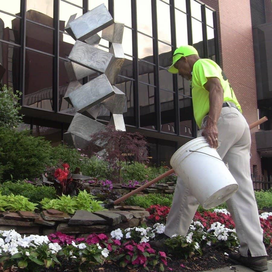 landscape maintenance crew picking up trash and debris out of landscaping beds
